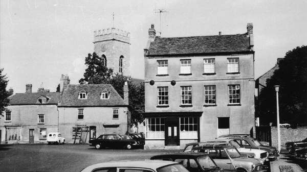 The Market Square in Stony Stratford looking to east side of Square old cottages with old van parked in front of the church tower behind large house to the left. Photo taken in 1971