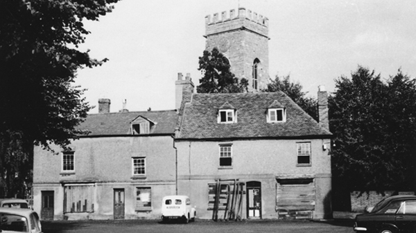 The Market Square, Stony Stratford looking to east side of Square old boarded up cottages now demolished and site of new library church tower behind. Photo taken in 1971