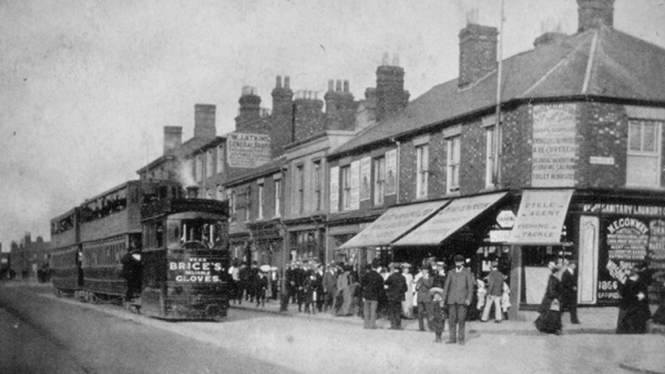 A view of Stratford Road, Wolverton at the turning for Radcliffe Street showing members of public visiting the local shops and the tram ferrying people west towards Stony Stratford, date unknown.