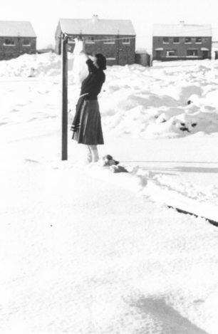 Vera Barrow pegging out washing during her first winter in Bletchley