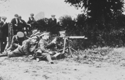 Local residents watching troops use an early machine gun