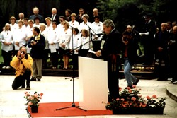 Colour photograph showing a man reading a speech possibly at a memorial