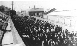 Black and white photograph of a parade of people marching past Wolverton Works.