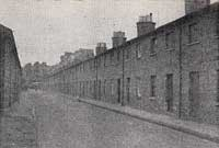 Black and white photograph of a street showing several houses on the right-hand side