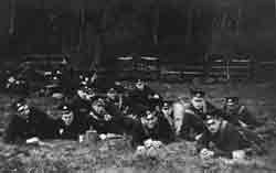 Black and white photograph showing several men in uniform laying down in a field.