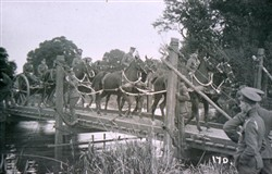 Slide of horse team and gun carriage on a bridge.