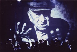 Photograph of a projection of a large image of Hawtin Mundy.