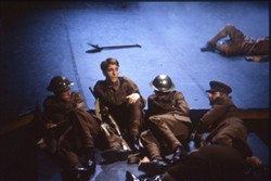 Colour slide of four soldiers lying on the floor.