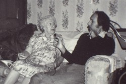 Slide of an elderly woman sat next to a man on a settee