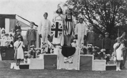 Photograph of 8 youths on a podium in fancy dress.