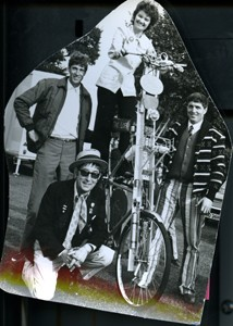 Bernice Edwards on a tall bicycle with three men at the Carnival.