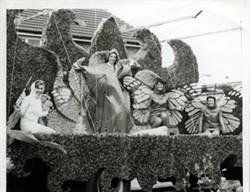 A carnival float of women dressed as butterflies.