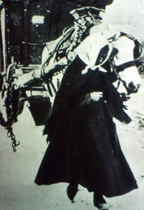 Slide of a woman leading a horse and cart