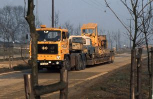 A yellow truck transporting a digger