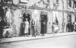 A number of decorated houses with their residents standing outside.