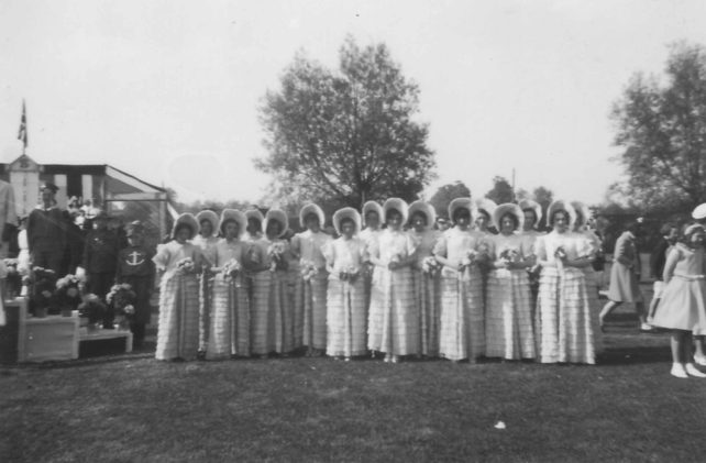 A group of 16 women dressed in identical bonnets and dresses with frilly skirts and bouquets