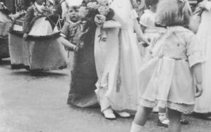 Carnival Procession with a young carnival queen and reluctant pageboy in a street