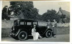 Photograph of a car and people.