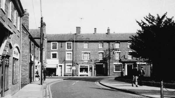 Stony Stratford, Church Street looking towards High Street and Bull Hotel churchyard on right and shops on left. Photo taken in 1971