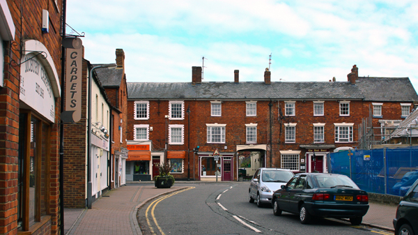 A modern view of Stony Stratford, Church Street looking towards High Street and Bull Hotel churchyard on right and shops on left. Photo taken in 2010 by Stephen Flinn