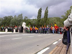 Colour photograph showing a parade approaching the Ploegsteert Memorial to the Missing at the Royal Berkshire Cemetery Extension.