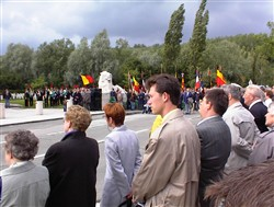 Colour photograph showing onlookers watching a parade approaching the Ploegsteert Memorial to the Missing at the Royal Berkshire Cemetery Extension.