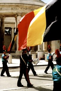 Colour photograph showing part of a parade band marching past the Ploegsteert Memorial to the Missing at the Royal Berkshire Cemetery Extension.