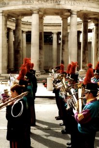 Colour photograph showing the brass section of a parade band marching past the Ploegsteert Memorial to the Missing at the Royal Berkshire Cemetery Extension.