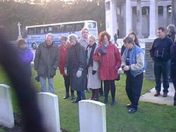 Colour photograph of a group of people looking at headstones at the Royal Berkshire Cemetery Extension.