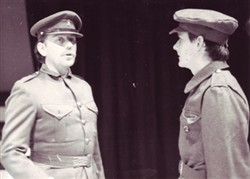 Photograph of two people dressed as soldiers talking to each other.