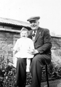 Photograph of elderly man holding a baby