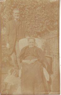 An elderly couple in a garden.