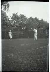Negative of two people playing Tennis.