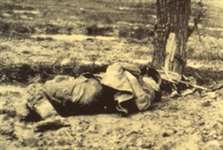 Slide of a photograph of a body of a soldier lying at the foot of a tree