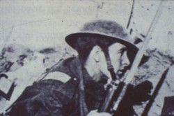 Slide of a photograph of a close up a soldier looking over a barricade.