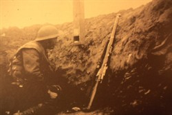 Slide of a photograph of a soldier looking through a periscope