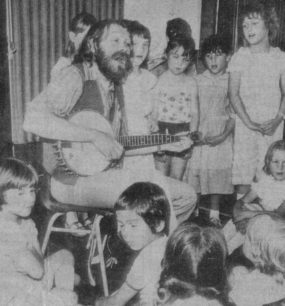 John Roberts with his guitar and a group of children