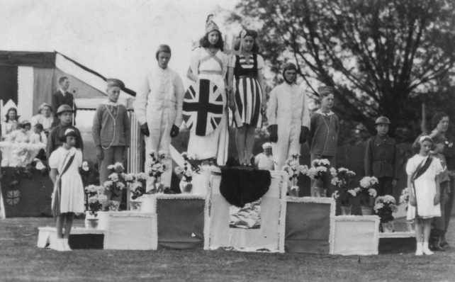 Photograph of eight youths on a podium in fancy dress.