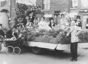 """Bill Alderman standing by one of the floats """"The English Garden""""."""