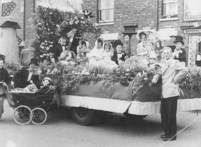 Bill Alderman standing by one of the floats