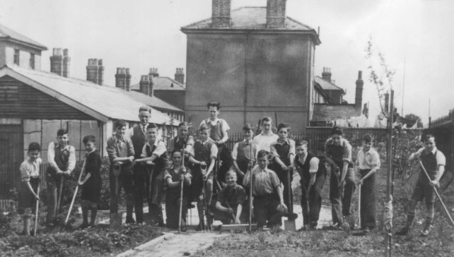 Group of boys gardening near Railway Cottages.