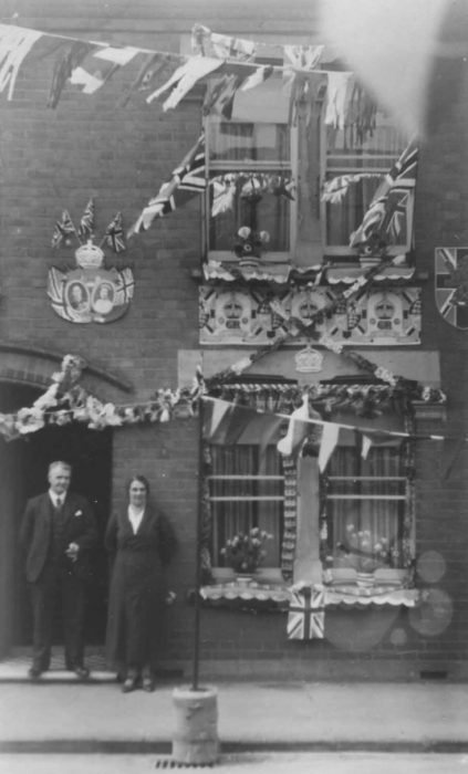 Couple standing in front of large house decorated  for a Coronation.