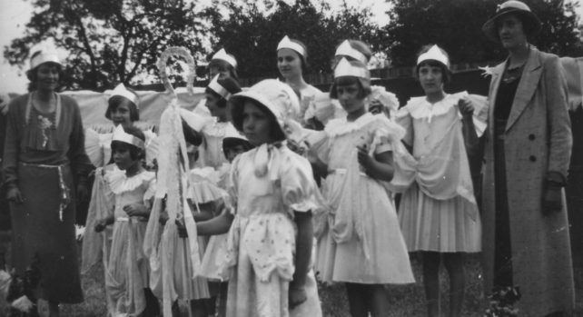 Group of ten girls dressed up (one as Bo Peep maybe) with two women