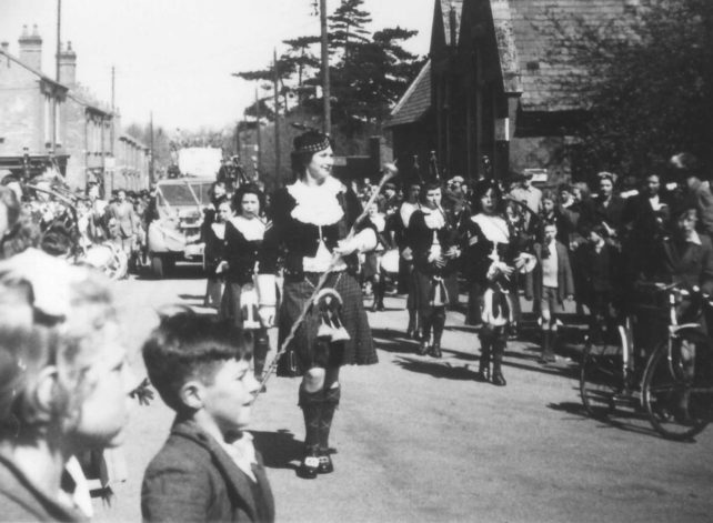 Girl pipers marching along a street.