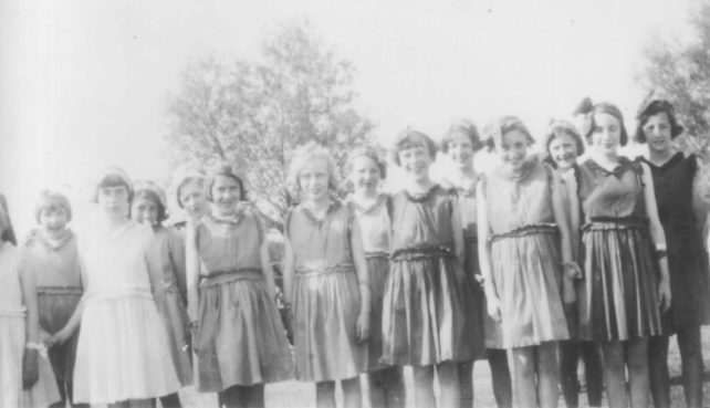 Group of 14 girls with matching dresses.
