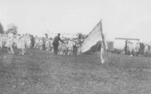 Groups of children dressed up in a field, getting ready for a parade maybe.