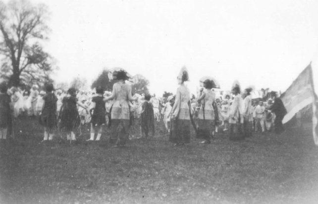 Groups of children and women in fancy dress in a field.