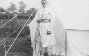 Man in Indian costume standing by a tent