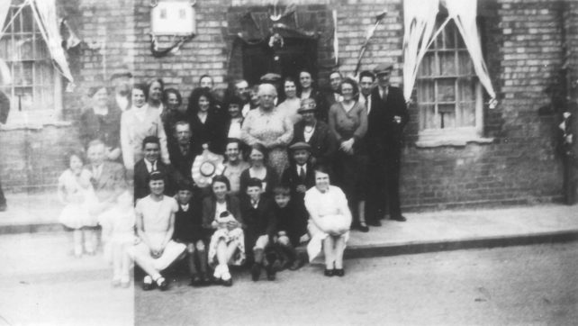 Group of adults and children posing in front of a decorated house.