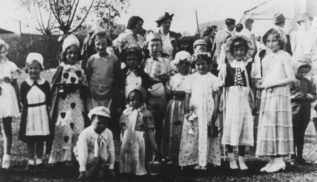 A group of children dressed in a variety of costumes